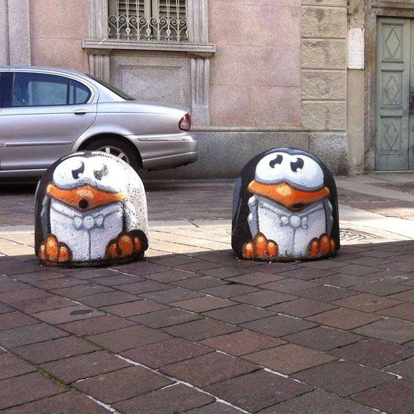 Three singing penguins, painted on street bollards in Como, Italy, by Pao.