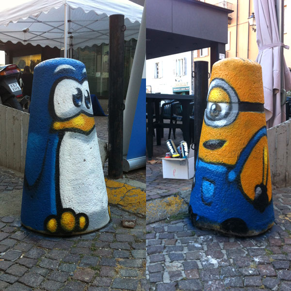 three bollards painted with penguin, minion and a robot character. Street art by Pao in Cuneo